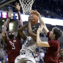 Temple forward Jake O'Brien, right, blocks a shot by Xavier guard Landen Amos, center, during the first half of an NCAA college basketball game, Thursday, Jan. 10, 2013, in Cincinnati. Temple forward Anthony Lee (3) helps. (AP Photo/Al Behrman)