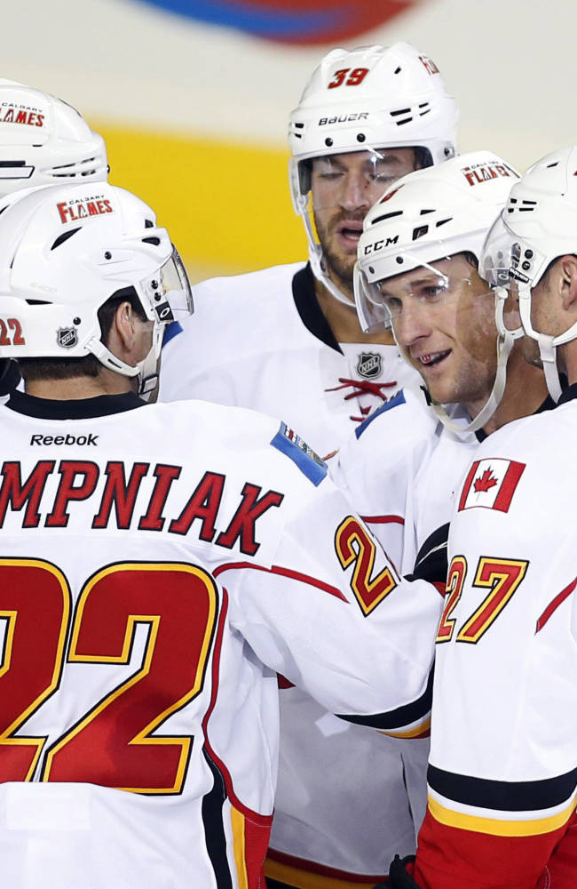 Calgary Flames' Dennis Wideman, second from right, celebrates his goal with teammates, from left, Lee Stempniak, TJ Galiardi and Derek Smith, during the second period of a split-squad preseason NHL hockey game against the New York Islanders in Calgary, Alberta, Tuesday, Sept. 17, 2013