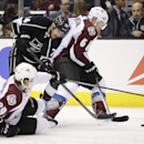 Los Angeles Kings' Dwight King, left, fights for the puck with Colorado Avalanche's Erik Johnson, right, and Nathan MacKinnon during the second period of an NHL hockey game on Saturday, Nov. 23, 2013, in Los Angeles The Associated Press