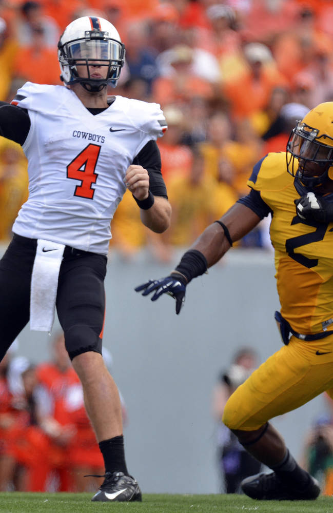 In this Sept. 28, 2013, file photo, Oklahoma State quarterback J.W. Walsh (4) attempts a pass as West Virginia's Brandon Golson rushes in during the second quarter of an NCAA college football game in Morgantown, W.Va. Walsh looked nearly unstoppable in his first few games this season for Oklahoma State. The quarterback, however, struggled in a loss last week at West Virginiam a lesson he hopes leads to a rebound this week against Kansas State