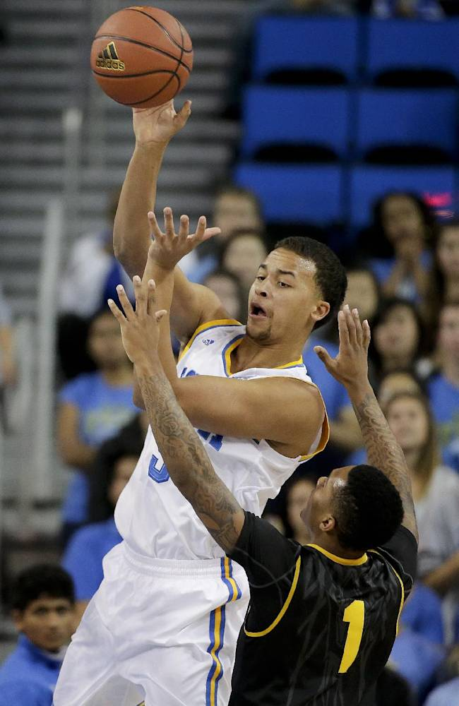 UCLA guard Kyle Anderson, left, passes over Arizona State guard Jahii Carson during the first half of an NCAA college basketball game in Los Angeles, Sunday, Jan. 12, 2014