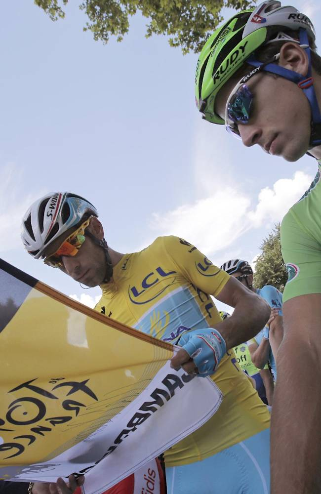 Peter Sagan of Slovakia, wearing the best sprinter's green jersey, watches as Italy's Vincenzo Nibali, left, signs the start flag prior to the start of the third stage of the Tour de France cycling race over 155 kilometers (96.3 miles) with start in Cambridge and finish in London, England, Monday, July 7, 2014