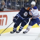 Edmonton Oilers' Andrew Ference (21) and Winnipeg Jets' Jacob Trouba (8) go for the loose puck during second period NHL action in Winnipeg, Manitoba, on Wednesday, Dec. 3, 2014 The Associated Press