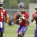 Minnesota Vikings quarterbacks Matt Cassel, center, and Christian Ponder, right, throw during a passing drill as fellow quarterback Teddy Bridgewater, left, stands near, during NFL football training camp, Friday, July 25, 2014, in Mankato, Minn The Associ