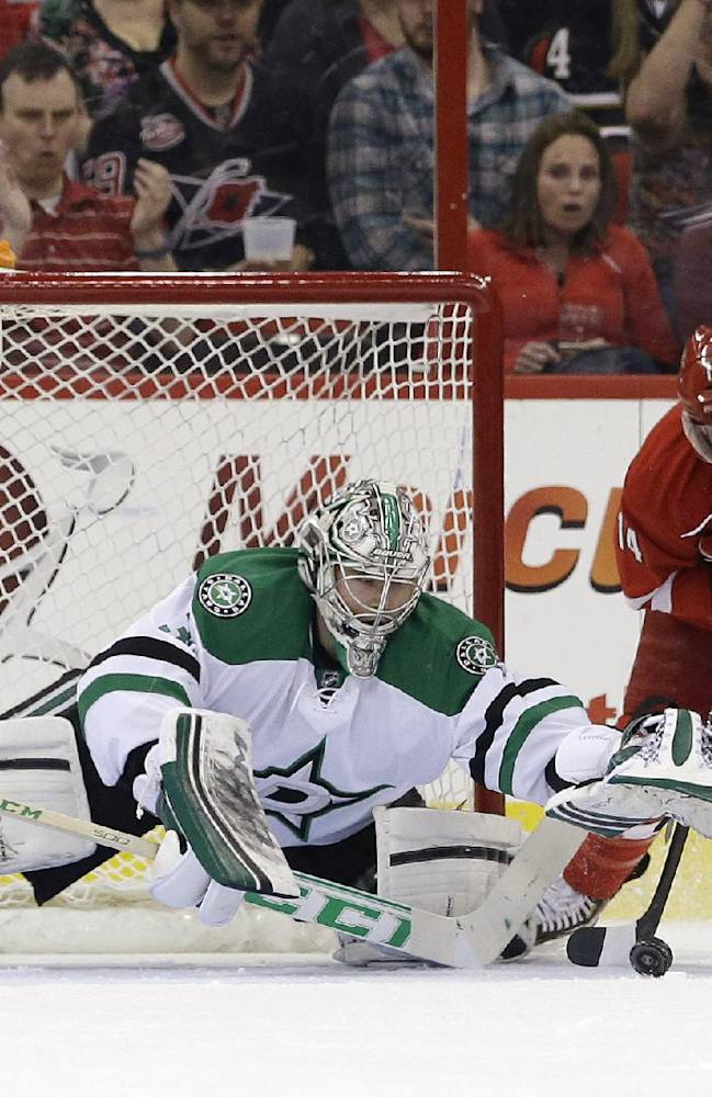 Dallas Stars goalie Kari Lehtonen, of Finland, and Stars' Jamie Benn (14) defend the goal against Carolina Hurricanes' Nathan Gerbe, middle, during the first period of an NHL hockey game in Raleigh, N.C., Thursday, April 3, 2014