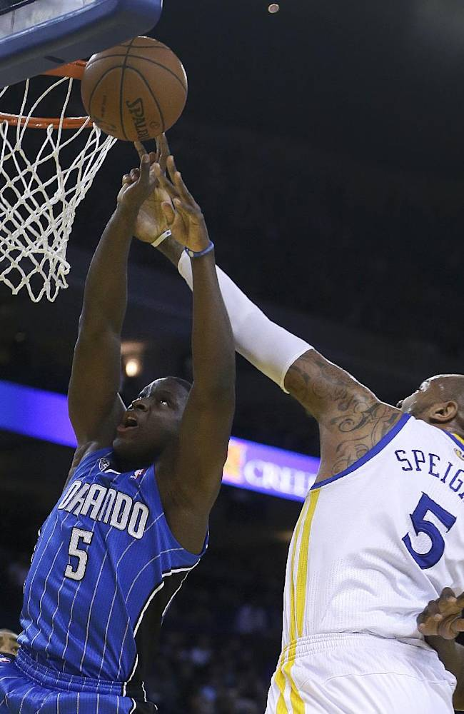 Orlando Magic's Victor Oladipo, left, lays up a shot against Golden State Warriors' Marreese Speights during the first half of an NBA basketball game Tuesday, March 18, 2014, in Oakland, Calif