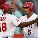 Los Angeles Angels' Torii Hunte (48) and Albert Pujols celebrate after scoring on Pujols' home run against the Texas Rangers in the seventh inning of a baseball game in Anaheim, Calif., Sunday, July 22, 2012. (AP Photo/Reed Saxon)