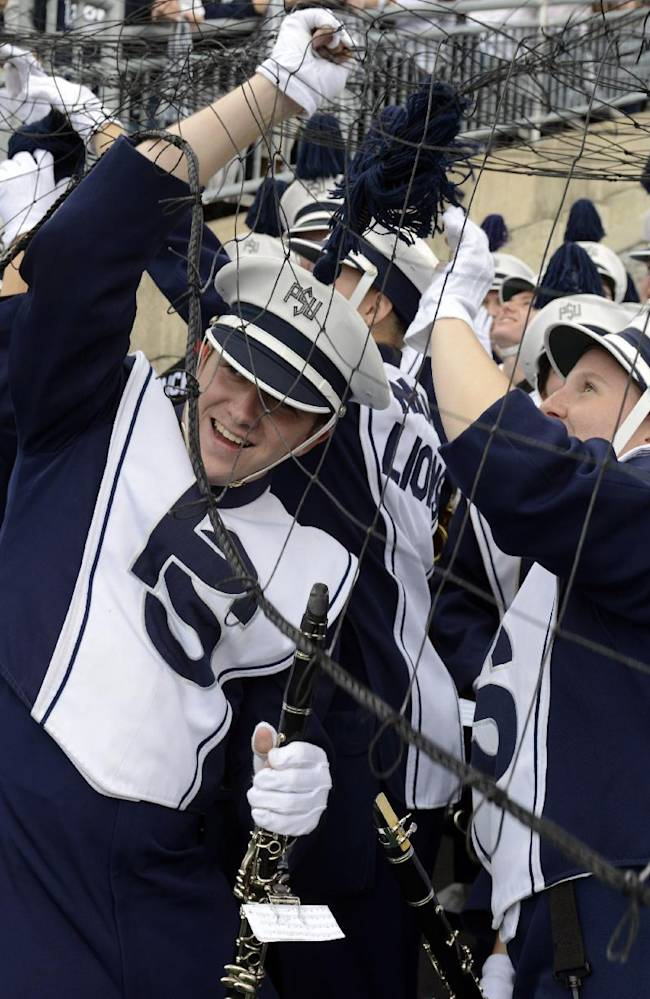 Members of Penn State's Blue Band get caught in the extra point net at Beaver Stadium before an NCAA college football game against Illinois in State College, Pa., Saturday, Nov. 2, 2013