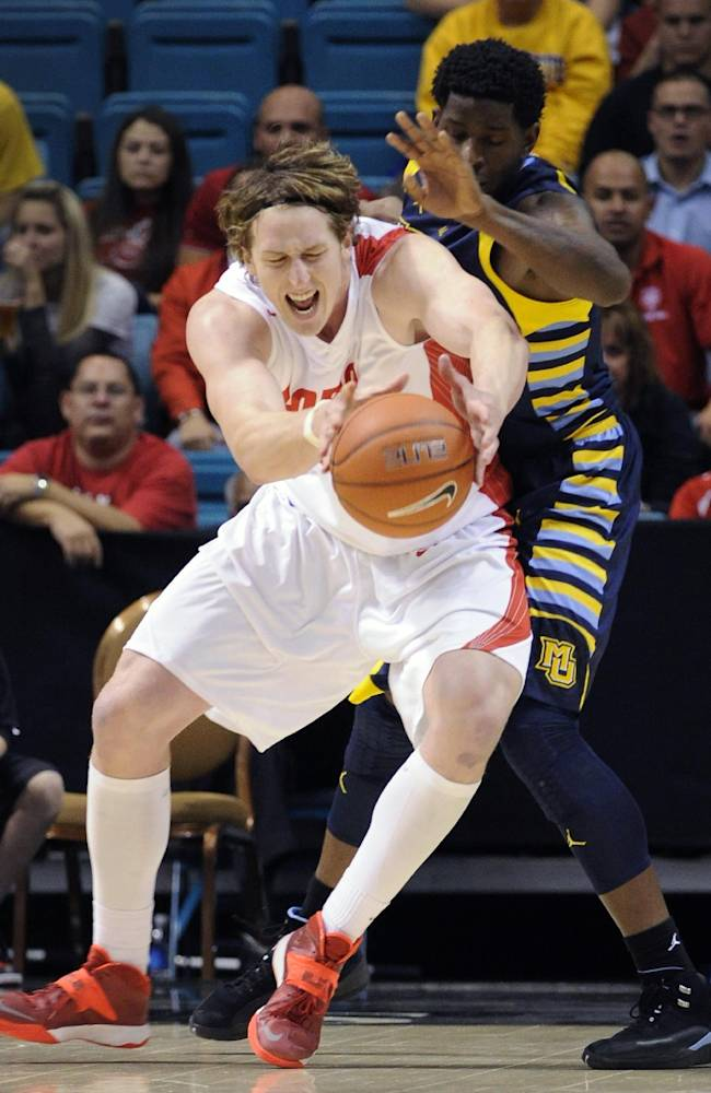New Mexico's  Cameron Bairstow, left, grabs a rebound against Marquette's Jamil Wilson during the second half of an NCAA college basketball game on Saturday, Dec. 21, 2013, in Las Vegas. New Mexico won 75-68