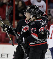 Carolina Hurricanes' Justin Faulk (27) congratulates Alexander Semin following Semin's goal against the Florida Panthers during the first period of an NHL hockey game in Raleigh, N.C., Friday, Feb. 7, 2014. Carolina won 5-1. (AP Photo/Gerry Broome)