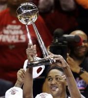 Indiana Fever forward Tamika Catchings hold up the trophy after defeating the Minesotta Lynx 87-78 in Game 4 of the WNBA basketball Finals, Sunday, Oct. 21, 2012, in Indianapolis. The Fever clinched their first WNBA championship. (AP Photo/AJ Mast)