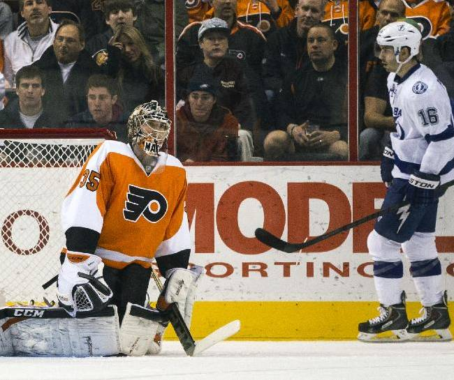 Tampa Bay Lightning's Teddy Purcell, right, skates after scoring on Philadelphia Flyers' Steve Mason, left, during the second period of an NHL hockey game, Saturday, Jan. 11, 2014, in Philadelphia