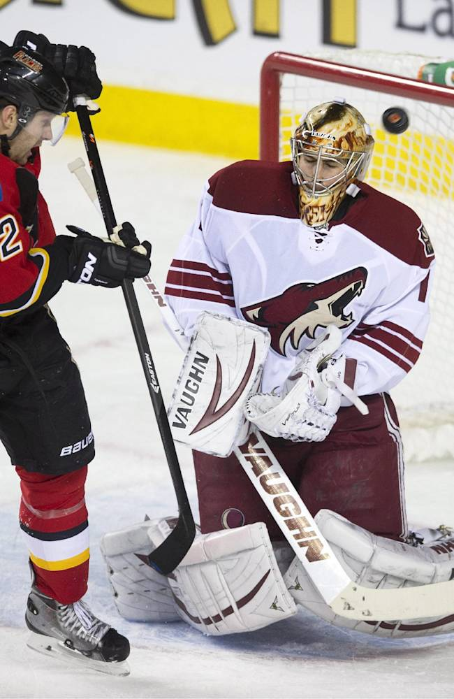 Phoenix Coyotes' goalie Thomas Greiss, right, from Germany, makes a save as Calgary Flames' Lee Stempniak looks for a rebound  during the first period of an NHL hockey game, Wednesday, Dec. 4, 2013 in Calgary, Alberta