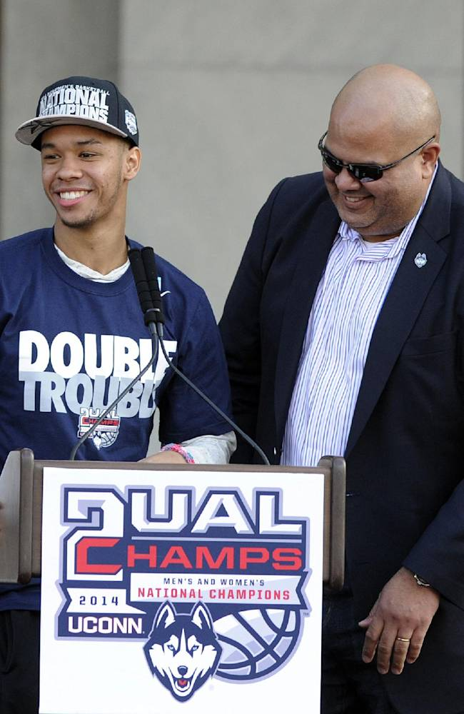 Connecticut director of athletics Warde Manuel, right, and men's basketball player Shabazz Napier smile during a rally at the State Capitol in Hartford, Conn., on Sunday, April 13, 2014, held to celebrate UConn's titles in the NCAA men's and women's basketball tournaments