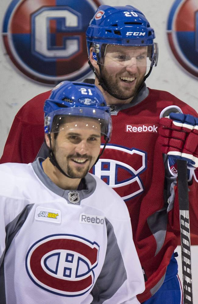 Montreal Canadiens captain Brian Gionta, front, and Thomas Vanek, of Austria, laugh during NHL hockey practice Wednesday, April 30, 2014, in Brossard, Quebec. The Canadiens face the Boston Bruins in Game 1 in the second round of the Stanley Cup playoffs Thursday in Boston