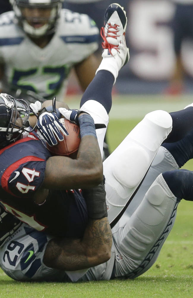 Houston Texans' Ben Tate (44) is stopped by Seattle Seahawks' Earl Thomas (29) during the first quarter an NFL football game Sunday, Sept. 29, 2013, in Houston