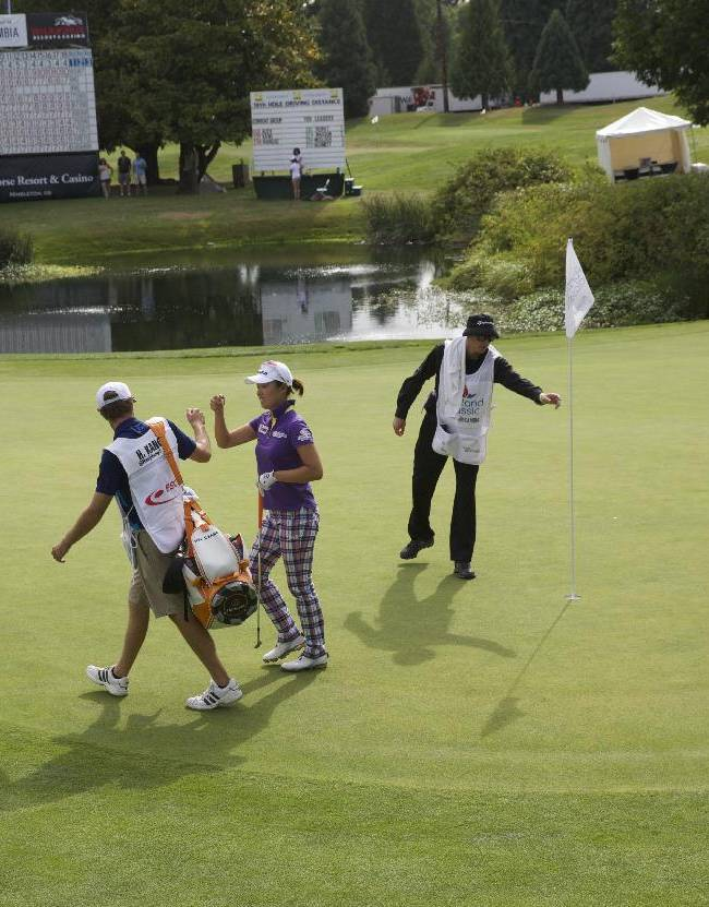 Hae Ji Kang celebrates witih her caddie after chipping in for a par during the second round of the Portland Classic LPGA golf tournament, Friday, Aug. 29, 2014, in Portland, Ore