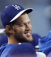 Los Angeles Dodgers pitcher Clayton Kershaw smiles in the dugout during the first inning against the Los Angeles Angels in an exhibition baseball game in Los Angeles, Thursday, March 27, 2014. (AP Photo/Danny Moloshok)