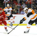 Philadelphia Flyers right wing Steve Downie (9) scores a goal as Detroit Red Wings defenseman Brendan Smith (2) defends in the first period of an NHL hockey game in Detroit, Wednesday, Dec. 4, 2013. (AP Photo/Paul Sancya)