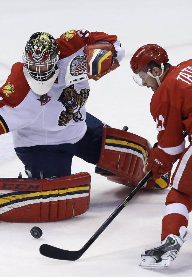 Florida Panthers goalie Tim Thomas (34) deflects a shot by Detroit Red Wings left wing Tomas Tatar (21) of the Czech Republic during the third period of an NHL hockey game in Detroit, Sunday, Jan. 26, 2014. Thomas stopped 26 shots in the Panthers 5-4 win in a shootout