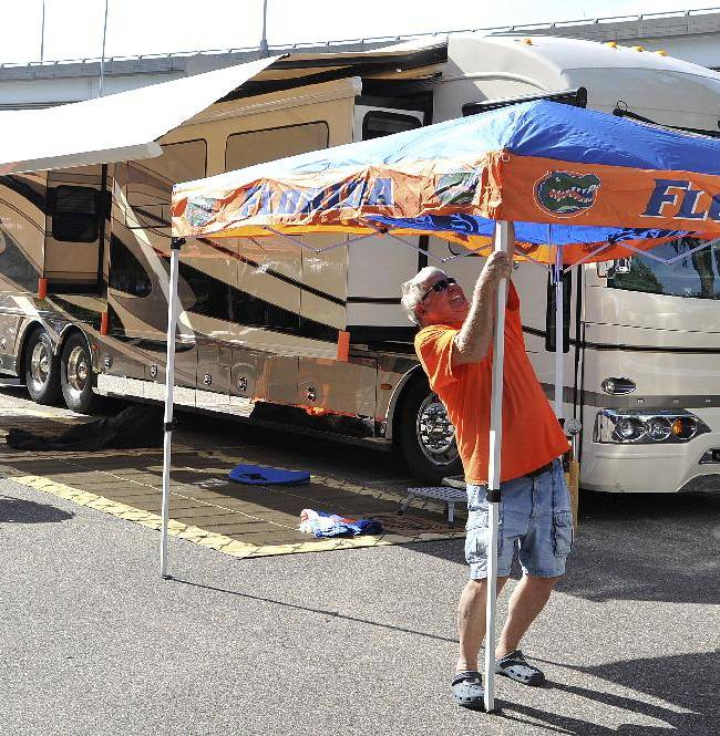 Gary, center, and Wynette Stotz, of New Smyrna Beach, Fla., set up their Florida canopy in an RV parking lot Wednesday, Oct. 30, 2013, in Jacksonville, Fla. Florida faces Georgia in an NCAA college football Saturday in Jacksonville