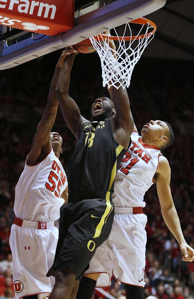 Oregon's Richard Amardi, center, puts a shot between Utah's Delon Wright, left, and Jordan Loveridge during the second half of an NCAA college basketball game in Salt Lake City, Thursday, Jan. 2, 2014. Oregon beat Utah in overtime, 70-68