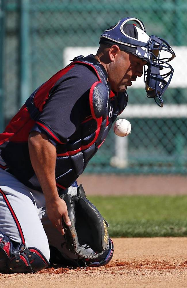 Atlanta Braves catcher Gerald Laird blocks the ball as it bounces off his mask during baseball spring training Tuesday, Feb. 18, 2014, in Kissimmee, Fla