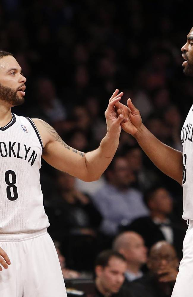 Brooklyn Nets' Deron Williams (8) celebrates with teammate Alan Anderson during the second half of an NBA basketball game against the San Antonio Spurs, Thursday, Feb. 6, 2014, in New York. Brooklyn won 103-89
