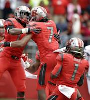 Teammates celebrate with Rutgers' Quron Pratt (7) after he ran a kick off back for a touchdown during the first half of an NCAA college football game against Eastern Michigan in Piscataway, N.J., Saturday, Sept. 14, 2013. (AP Photo/Mel Evans)