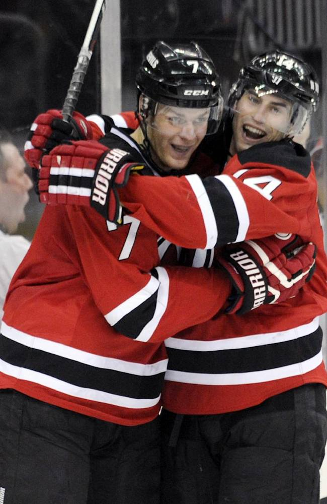 New Jersey Devils' Mark Fayne, left, celebrates with Adam Henrique after Fayne scored during the second period of an NHL hockey game Thursday, March 20, 2014, in Newark, N.J
