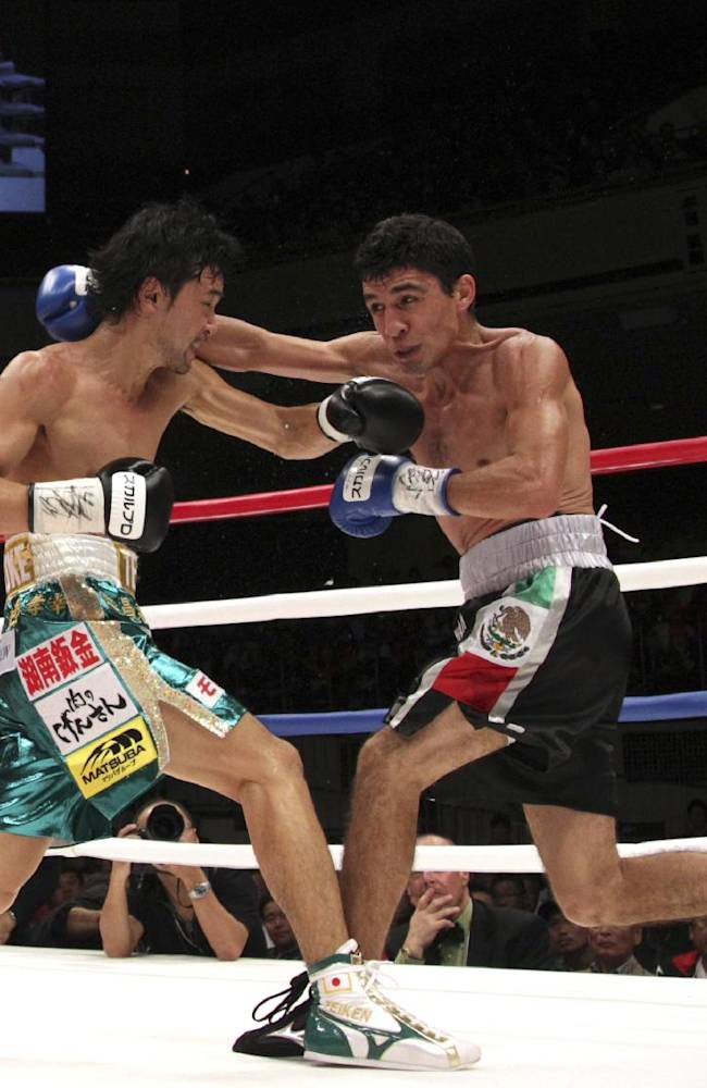 Japanese champion Shinsuke Yamanaka, left, and Mexican challenger Alberto Guevara exchange their punches in the fourth round of their WBC bantamweight title bout in Tokyo, Sunday, Nov. 10, 2013. Yamanaka knocked out Guevara in the ninth round to defend his title