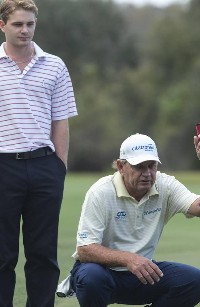 Greg Price watches his father Nick Price prepare to putt on the 10th hole during the Father-Son Challenge at the Ritz-Carlton Golf Club in Orlando, Fla., Sunday, Dec. 15, 2013