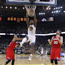 Golden State Warriors' Harrison Barnes (40) dunks over Philadelphia 76ers' Evan Turner (12) and Spencer Hawes (00) during the second half of an NBA basketball game on Monday, Feb. 10, 2014, in Oakland, Calif. Golden State won 123-80 The Associated Press