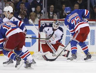 Columbus Blue Jackets goalie Curtis McElhinney saves a shot on goal from New York Rangers' Brad Richards (19) as Ryan McDonagh (27) looks on during the first period of an NHL hockey game Thursday, Dec. 12, 2013, in New York. (AP Photo/Jason DeCrow)