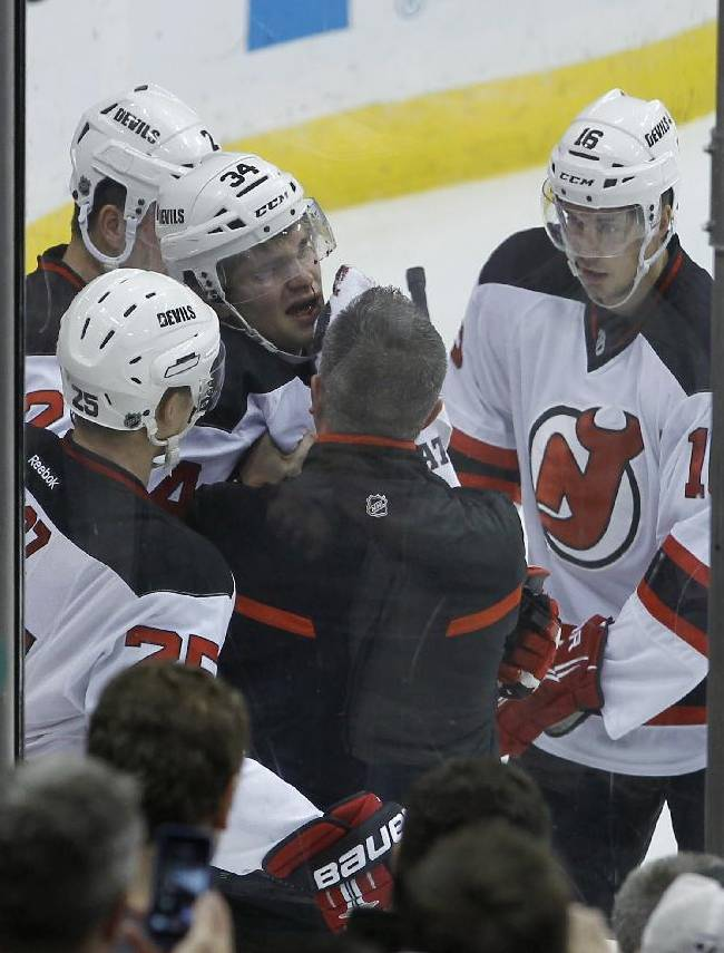 New Jersey Devils defenseman Jon Merrill (34) is helped up from the ice after he was tripped by Minnesota Wild center Torrey Mitchell during the first period of an NHL hockey game in St. Paul, Minn., Sunday, Nov. 3, 2013. Merrill left the game