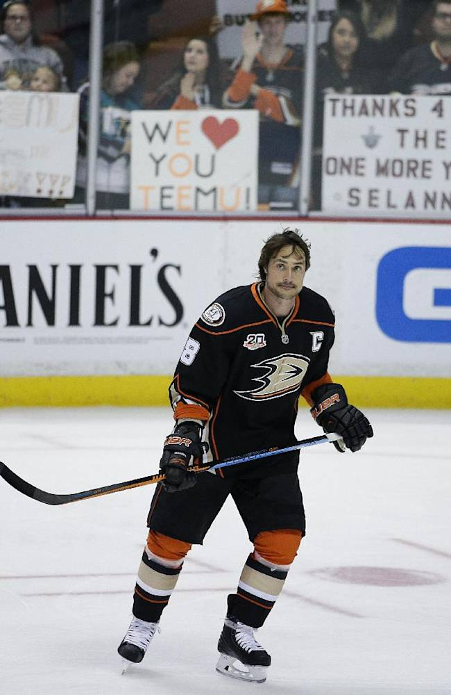 Anaheim Ducks' Teemu Selanne, of Finland, skates by as fans hold up signs for him during practice for an NHL hockey game against the Colorado Avalanche on Sunday, April 13, 2014, in Anaheim, Calif. Selanne plays his final regular-season game Sunday night