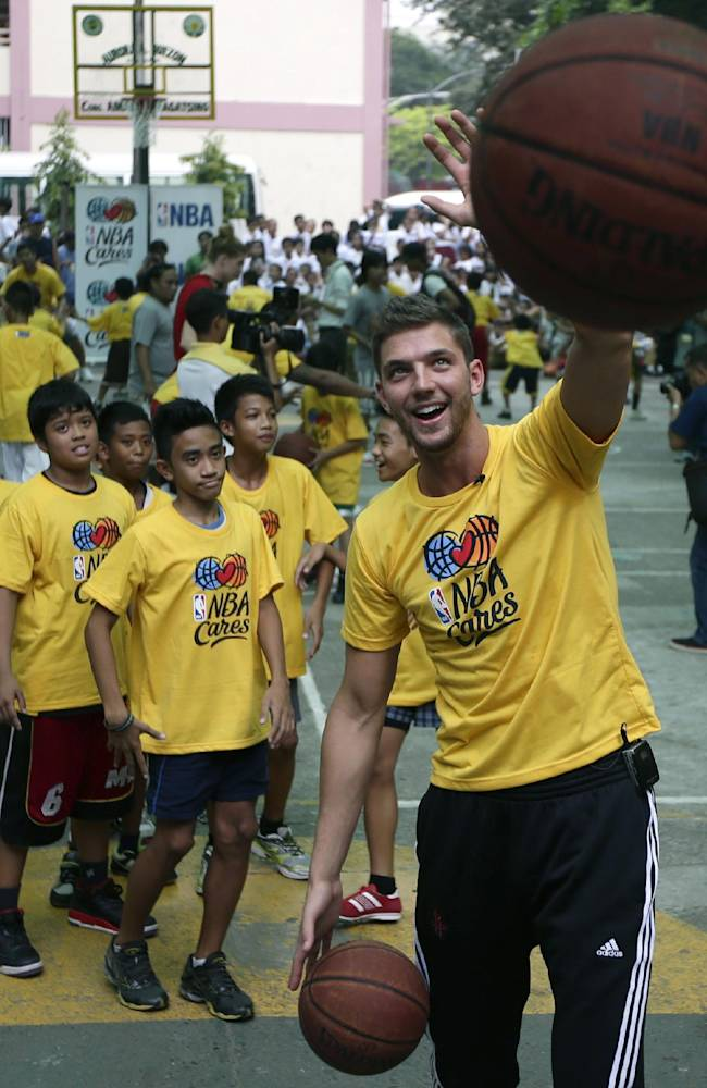 Houston Rockets' Chandler Parsons cheers after an elementary student he is teaching scored during a basketball clinic at Aurora Quezon Elementary School Wednesday, Oct. 9, 2013, in Manila, Philippines. The Indiana Pacers will play against the Houston Rockets on Thursday in the first NBA game in this basketball-obsessed Southeast Asian nation, part of the NBA's global schedule that will have eight teams play in six countries this month