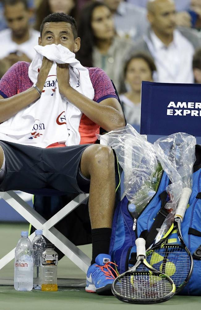 Nick Kyrgios, of Australia, wipes his face during a break in the action against Tommy Robredo, of Spain, in the third round of the U.S. Open tennis tournament early Sunday, Aug. 31, 2014, in New York