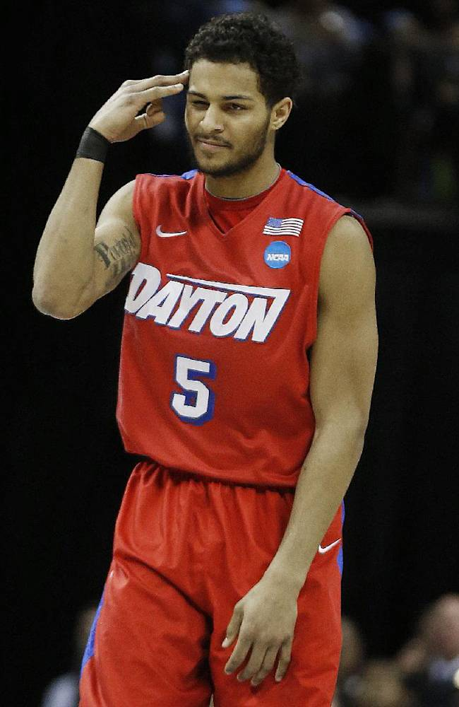 Dayton forward Devin Oliver (5) celebrates his three-point shot against Florida during the first half in a regional final game at the NCAA college basketball tournament, Saturday, March 29, 2014, in Memphis, Tenn