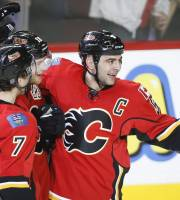 Calgary Flames' Matt Stajan, center, celebrates his goal with teammates TJ Brodie, left, and Mark Giordano during second period NHL hockey action in Calgary, Canada, Wednesday, Jan. 22, 2014. (AP Photo/The Canadian Press, Jeff McIntosh)