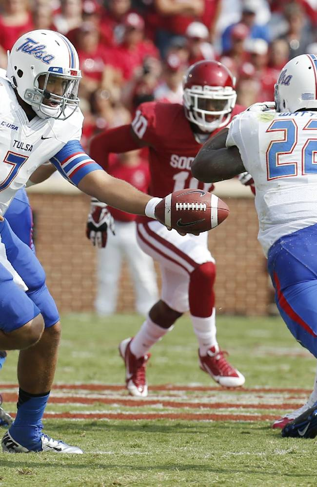 Tulsa quarterback Cody Green (7) hands off to Trey Watts (22) in the first quarter of an NCAA college football game against Oklahoma in Norman, Okla., Saturday, Sept. 14, 2013