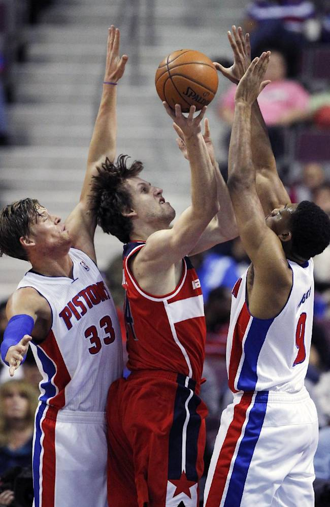 Washington Wizards forward Jan Vesely (24) tries to get a shot off against Detroit Pistons forwards Jonas Jerebko (33), of Sweden, and Tony Mitchell (9) during the second half of a preseason NBA basketball game Tuesday, Oct. 22, 2013, in Auburn Hills, Mich