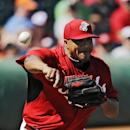 Cincinnati Reds relief pitcher Alfredo Simon fires to first to hold Cleveland Indians' Michael Brantley close in the third inning of a spring exhibition baseball game Monday, March 24, 2014, in Goodyear, Ariz The Associated Press