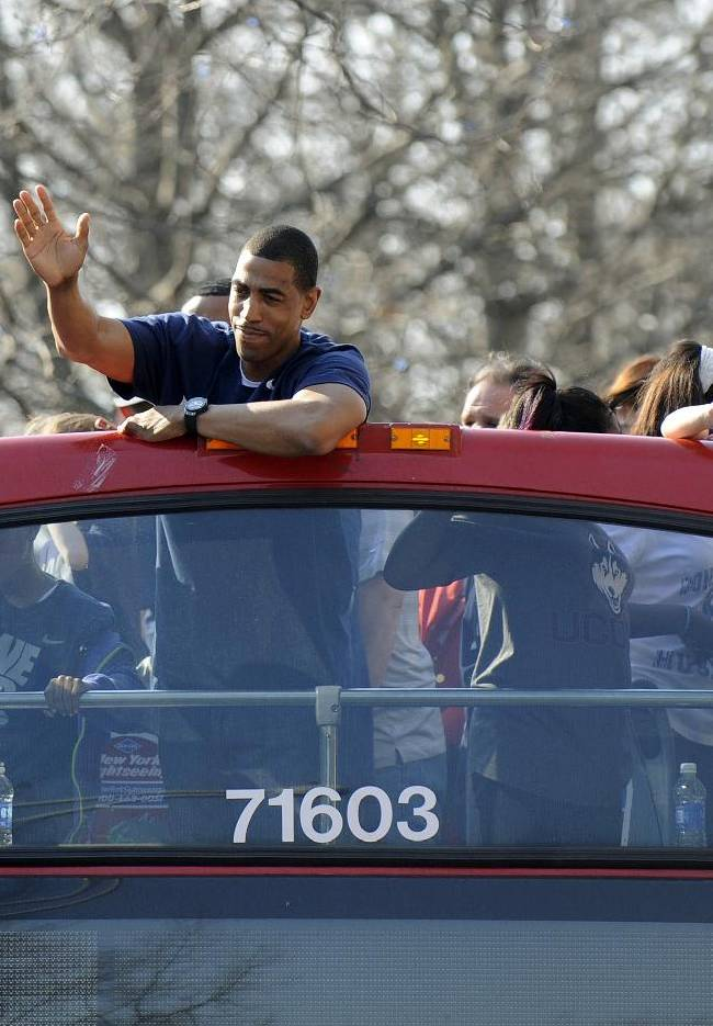 Connecticut men's basketball coach Kevin Ollie waves to a crowd during a parade in Hartford, Conn., on Sunday, April 13, 2014, celebrating UConn's wins in the NCAA men's and women's tournaments earlier this month