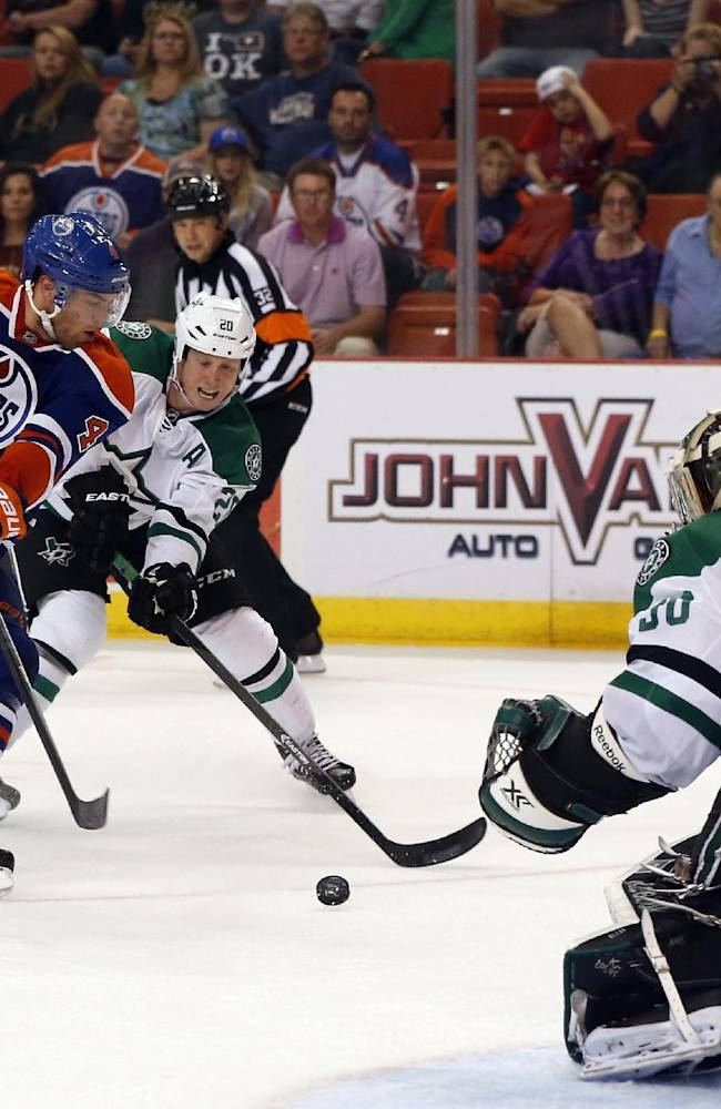 Dallas Stars center Cody Eakin (20), of Canada, breaks up a shot by Edmonton Oilers left wing Taylor Hall (4), also of Canada, in the second period of an NHL preseason hockey game in Oklahoma City, Friday, Sept. 27, 2013. Stars goalie Dan Ellis (30), right, watches the play