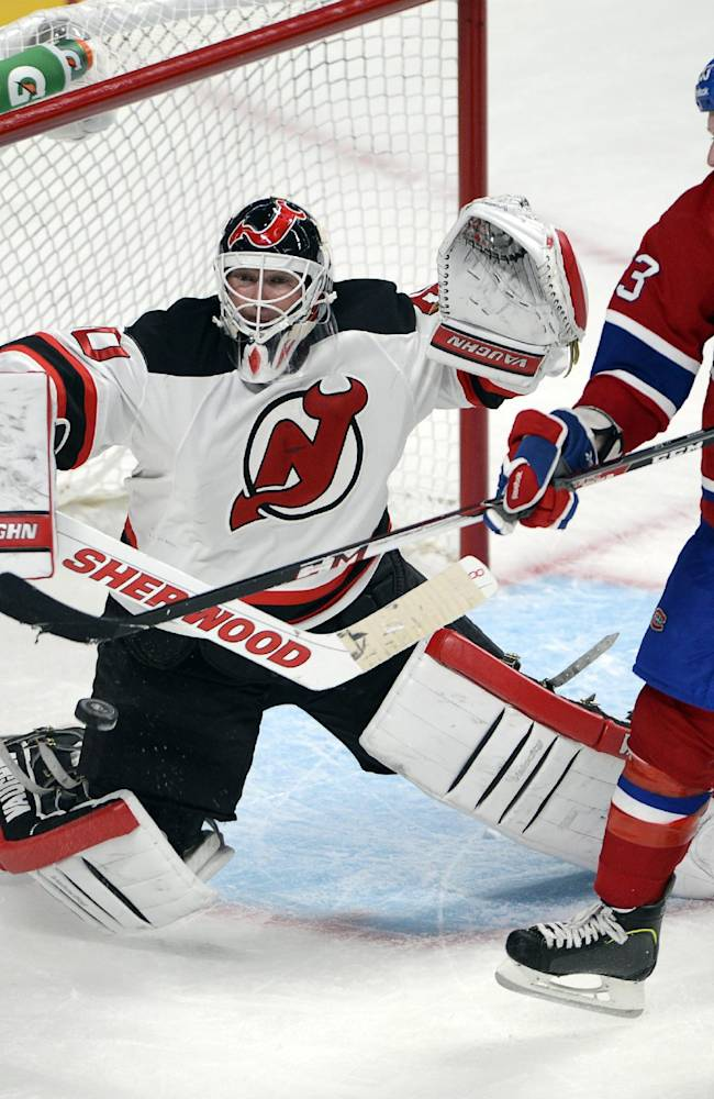 Montreal Canadiens' Ryan White deflects the puck past New Jersey Devils goaltender Martin Brodeur to score during the third period of an NHL hockey preseason game Monday, Sept. 23, 2013, in Montreal. The Canadiens won 3-2