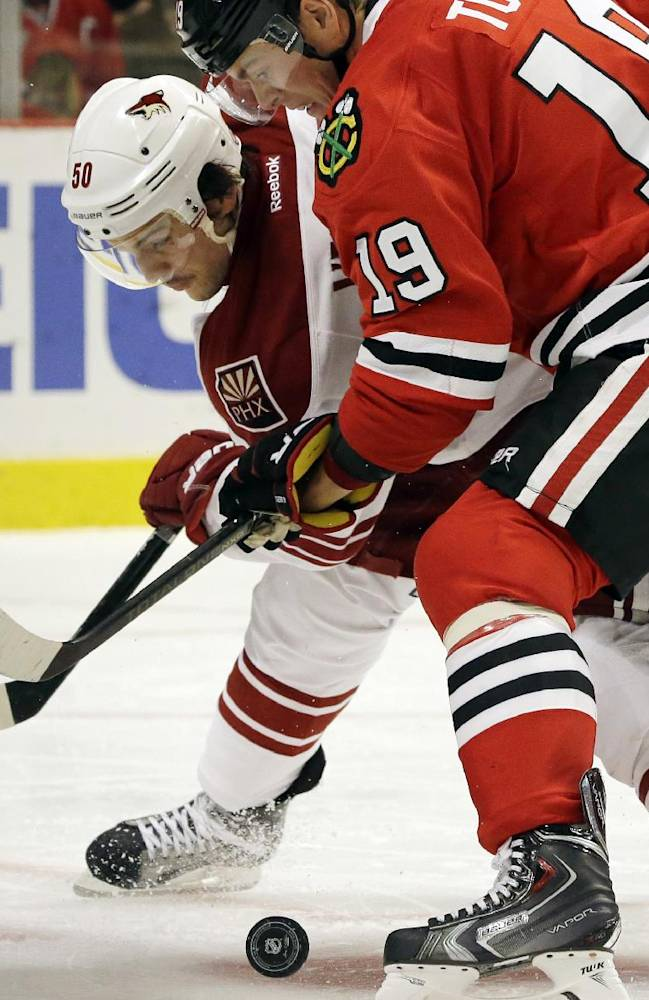 Chicago Blackhawks' Jonathan Toews, right, and Phoenix Coyotes' Antoine Vermette battle for the puck during the second period of an NHL hockey game in Chicago, Thursday, Nov. 14, 2013