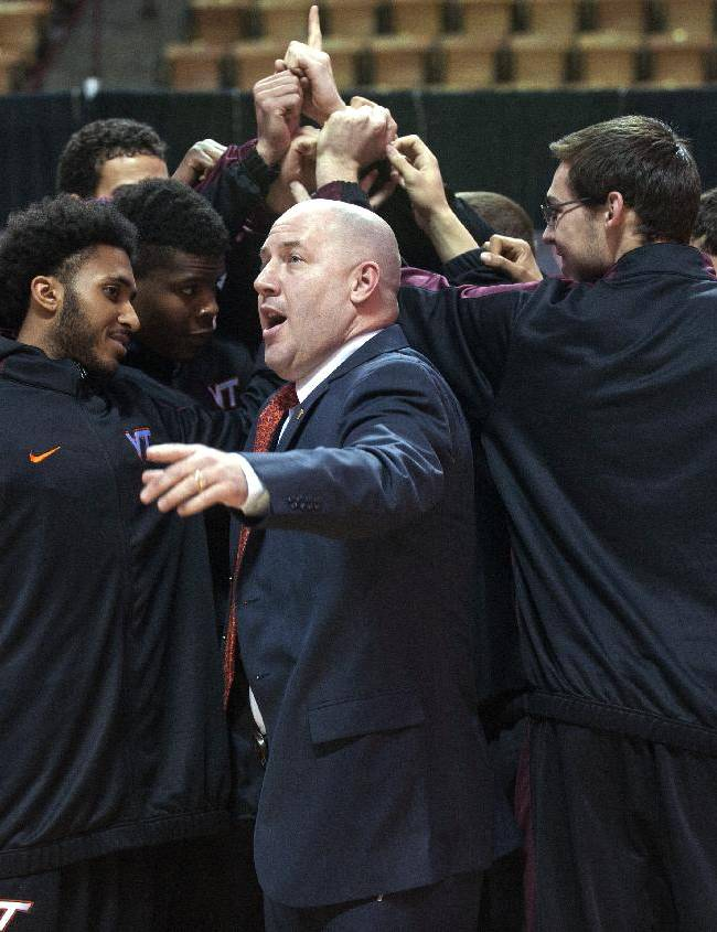 Marquette's former men's head basketball coach and now Virginia Tech's new men's head basketball coach, Buzz Williams does a Hokie chant with teram members at a news conference held at Cassell Coliseum, in Blacksburg, Virginia, Monday, March 24, 2014