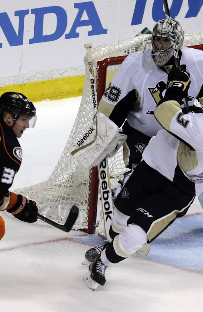 Anaheim Ducks right winger Jakob Silfverberg (33), of Sweden, and Pittsburgh Penguins defenseman Olli Maata (3), of Finland, and goalie Marc-Andre Fleury (29) skate in the second period of an NHL hockey game in Anaheim, Calif., Friday, March 7, 2014