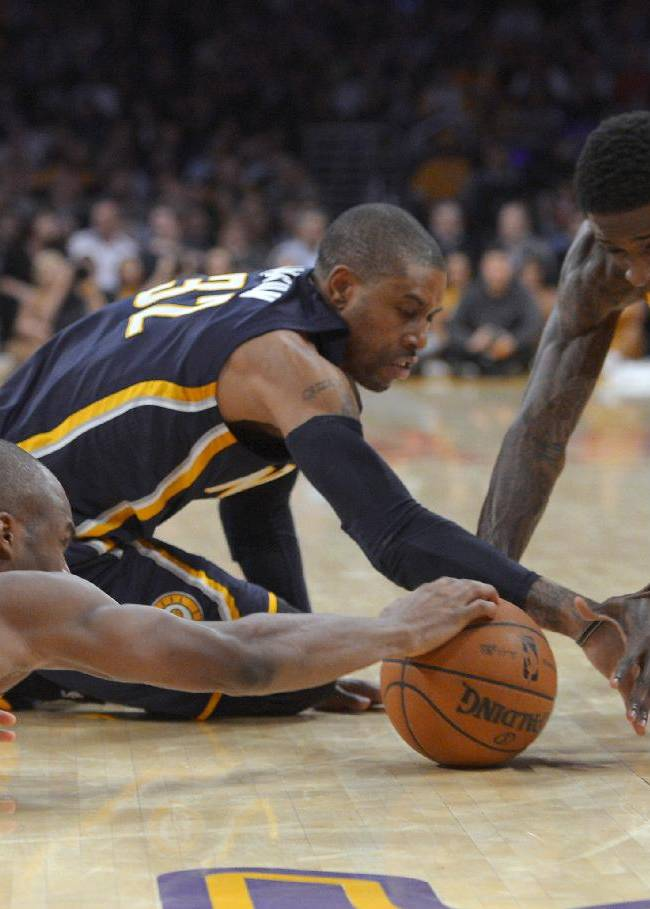 Los Angeles Lakers guards Jodie Meeks, left, and Manny Harris, right, compete for a loose ball with Indiana Pacers guard C.J. Watson during the first half of an NBA basketball game, Tuesday, Jan. 28, 2014, in  Los Angeles